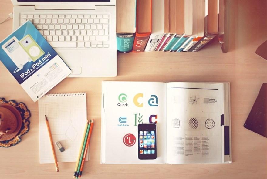 laptop books iPhone on desk