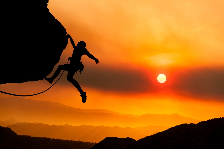 rock climber gripping edge of cliff against sunset