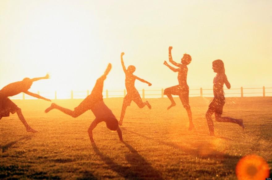 children playing in sprinkler summer sunset