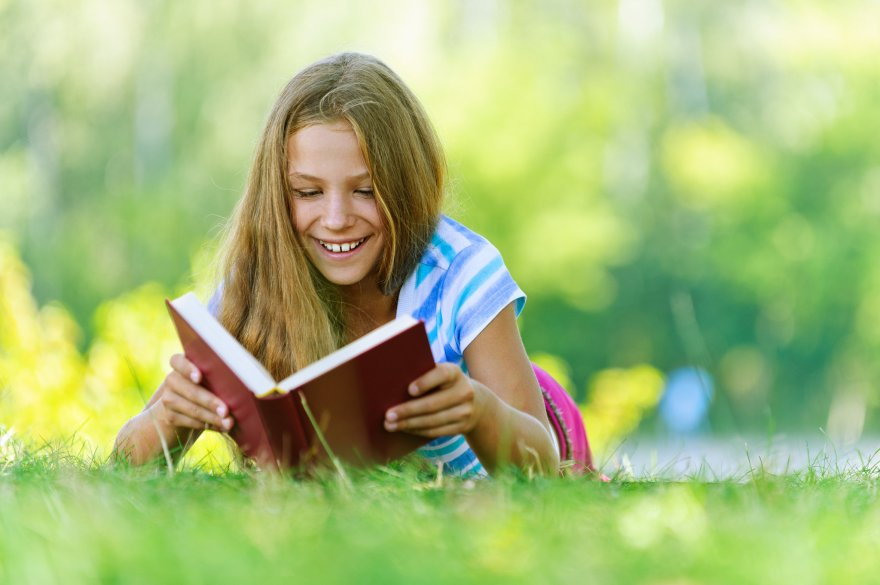 Girl reading book in grass during summer.